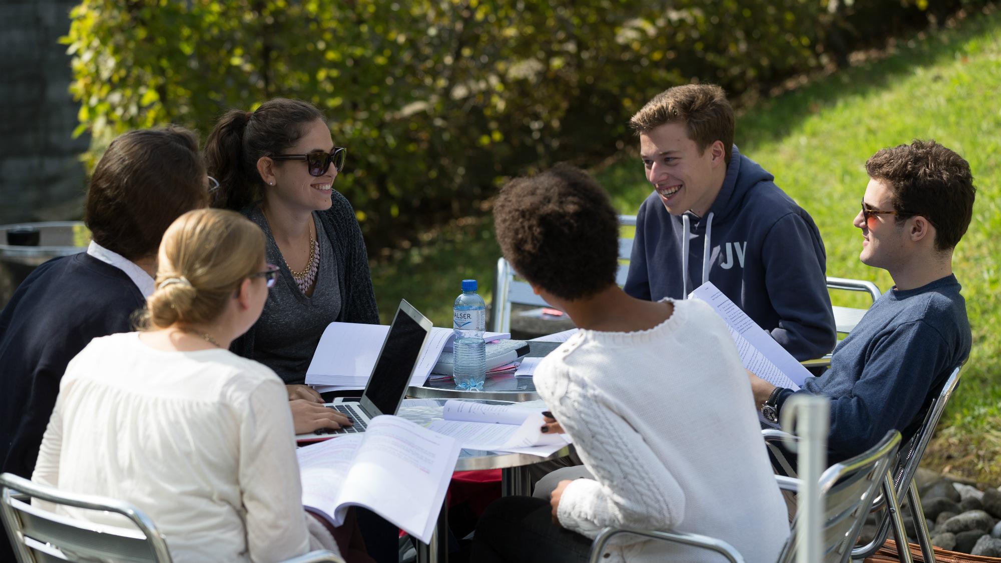 Studierende an der Sonne sitzend, zwischen Hauptgebaeude und Bibliotheksgebaeude der Universitaet St.Gallen (HSG)